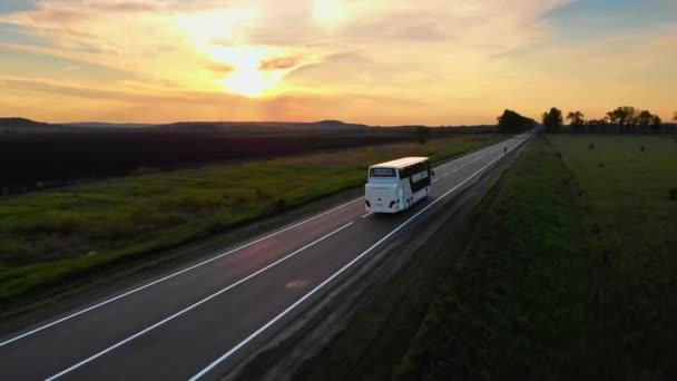 Letecký Drone View: Bílý turistický autobus odjíždí na cestu.