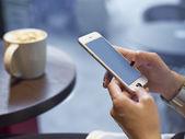Fotografie Mladá dívka si hraje smartphone v kavárně