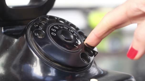 Wählen mit einem Retro-Telefon, Frau im Büro wählt das alte Telefon