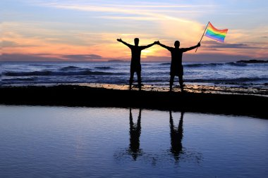 Gay men holding a pride flag.