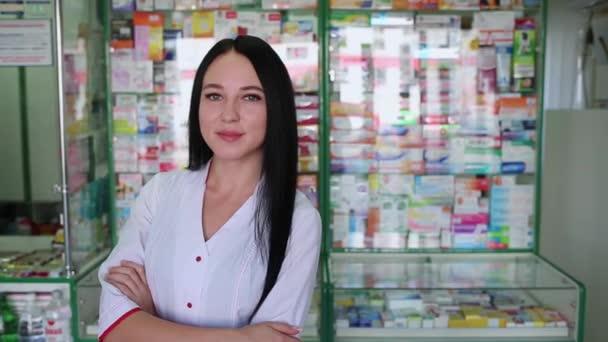 Eine schöne brünette Frau, die als Apothekerin arbeitet, posiert vor dem Hintergrund eines Apothekenfensters.