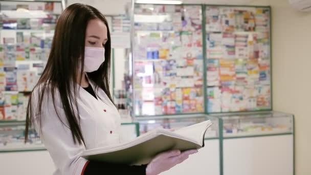 Eine Frau in medizinischer Maske, Bademantel und Handschuhen, liest in einem Ordner Zeitungen. Im Hintergrund Vitrinen mit Medikamenten. Konzept einer Virenpandemie und Schutz vor Infektionen.