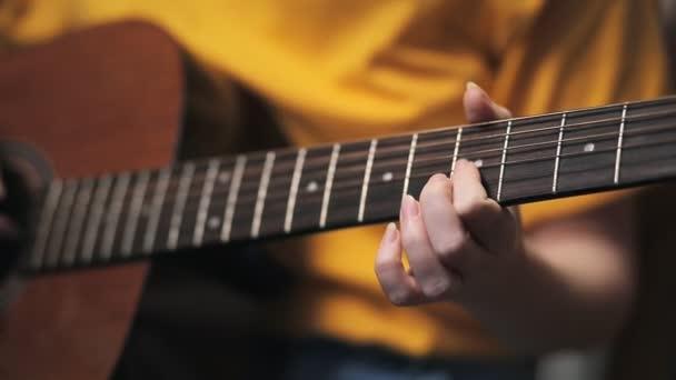 Ženská ruka svírá popruhy na kytaře. Ruce zblízka. Naučit se hrát na kytaru.