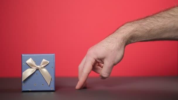 Die Hand eines Mannes nähert sich dem Geschenk mit den Fingern und stellt einen zweifelnden kleinen Mann dar. Roter Hintergrund, Nahaufnahme. Konzept von Feiertagen und Geschenken.