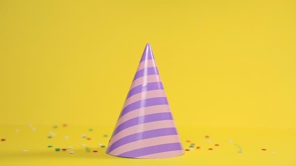 Festlicher, mehrfarbiger Hut aus Papier, steht auf gelbem Hintergrund. Konfetti fällt von oben. Urlaubskonzept.