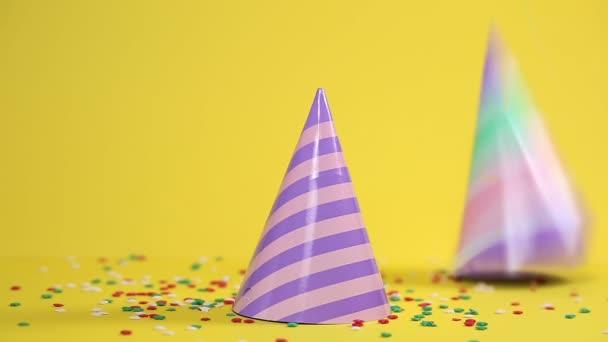 Ünnepi papír sokszínű kalapok esnek a konfetti tetejére. Sárga háttér. Üdülési koncepció.