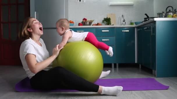 Sporttraining zu Hause. Eine junge Mutter macht Übungen mit einem Fitball und rollt ihr Kind auf dem Ball. Das Konzept des Sporttrainings mit Kindern.