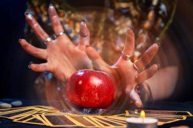 Bir falcı, Tarot kartlarının üzerinde duran kırmızı bir elmayı ortaya çıkarır. Meyveden sihirli bir aura çıkıyor. Kapatın. Kehanet, astroloji ve ezoterizm kavramı..