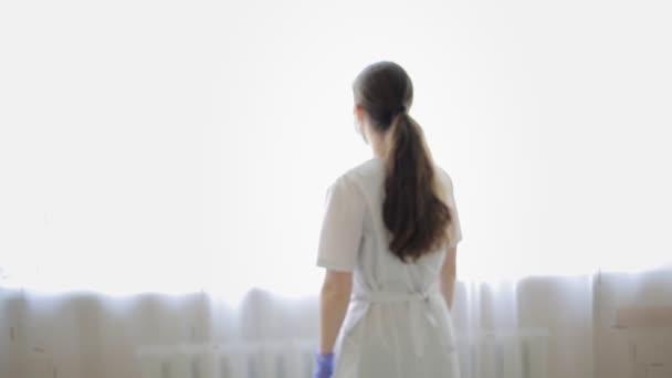 Covid-19. Die Ärztin mit Labormantel, OP-Maske und Handschuhen steht am Fenster, dreht sich um und nähert sich mit verschränkten Armen posierend. Ärzte bei der Arbeit in einem Krankenhaus während einer Virenpandemie.