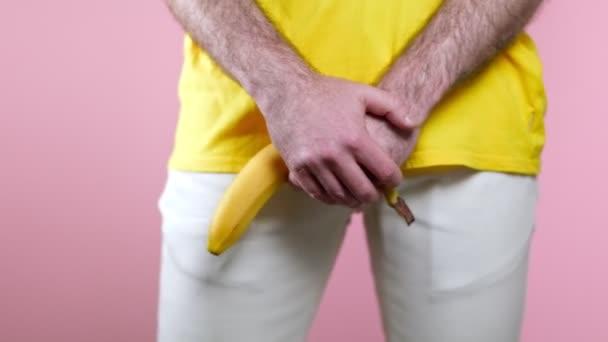 Impotenz. Der Mann hält eine gesenkte Banane in den Händen auf Höhe der Genitalien und schwankt leicht mit den Hüften. Aus nächster Nähe. Rosa Hintergrund. Das Konzept der Männergesundheit.