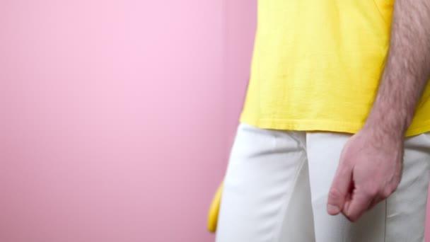 Ein Mann zeigt eine Banane in den Händen auf Höhe der Genitalien. Seitenansicht. Rosa Hintergrund. Das Konzept der Gesundheit und Potenz von Männern.