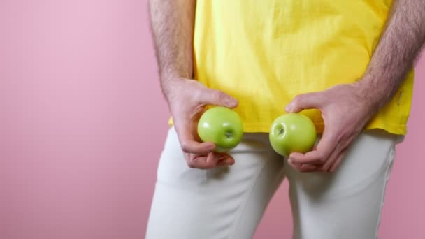 Potency. Man holds the apples in his hands at the level of the genitals and twists them. Close-up. Pink background. The concept of mens health.