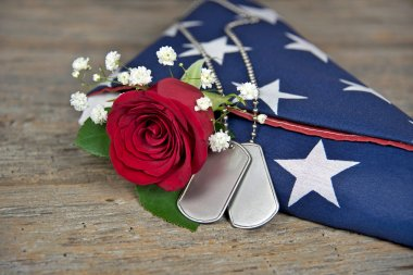 rose and dog tags on flag