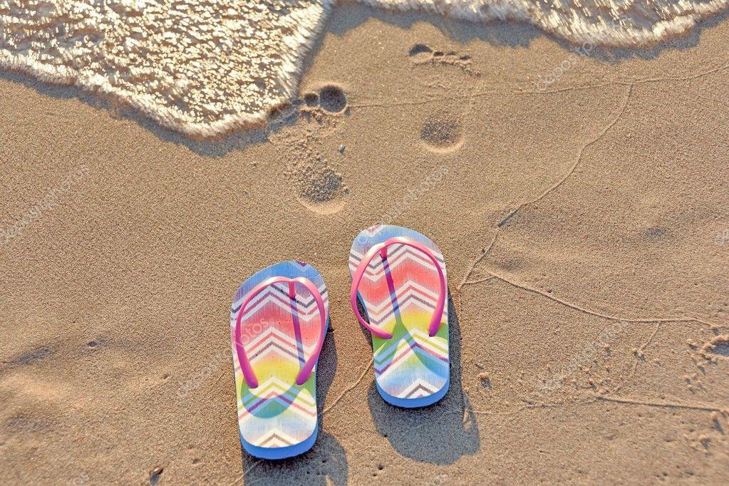 Paio di infradito e orme nella sabbia della spiaggia con surf schiumoso —  Foto di jentara 88c3b631f54