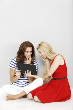 Two friends using a computer tablet