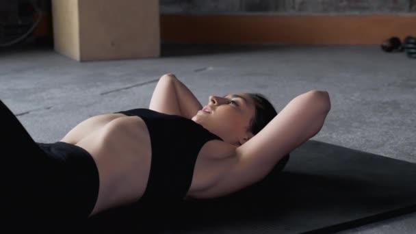 Detailní atletická dívka ve sportovním oblečení pumpuje břišní svaly. Sporty woman is doing abs exercises crunches on floor on mat in gym, side view. Sport a fitness. Školení, cvičení a wellness koncept.
