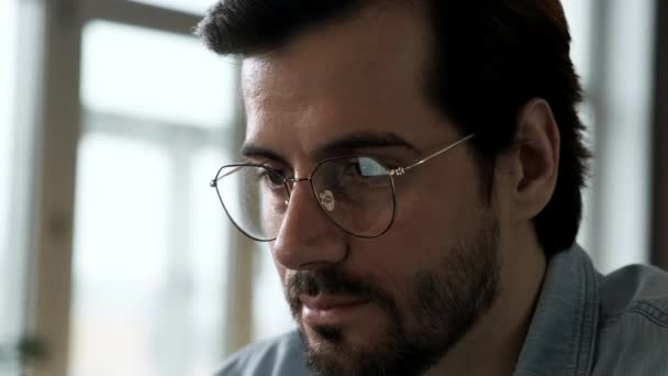 Spiegelungen des Laptop-Bildschirms in der Männerbrille. Porträt eines jungen kaukasischen freiberuflichen Geschäftsmannes, der im Büro arbeitet und im Internet surft. Hacker am Werk stehlen Konten-Datenbank.
