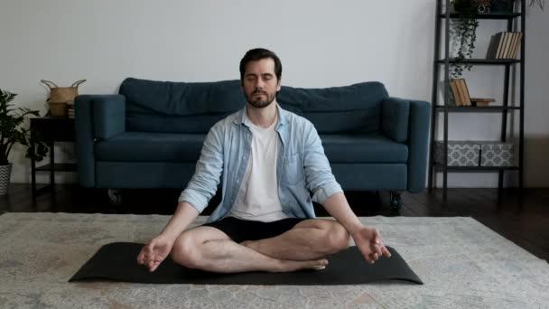 Ein junger Mann macht Yoga im Lotus-Sitzen und macht Atem- und Denkübungen