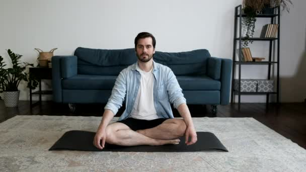 Entspannter Mann sitzt in Lotus-Pose auf Yogamatte im Wohnzimmer und atmet.