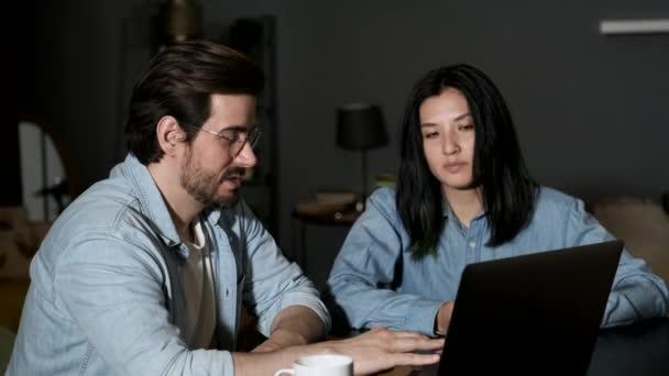 Porträt eines jungen Paares, das zu Hause vor einem Notizbuch sitzt. Schöne brünette mann und süß frau working bei laptop.
