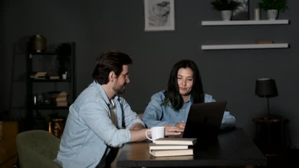 Ein junger Mann und eine Kollegin diskutieren über ein Online-Projekt, zwei Manager arbeiten zu Hause und benutzen einen Laptop