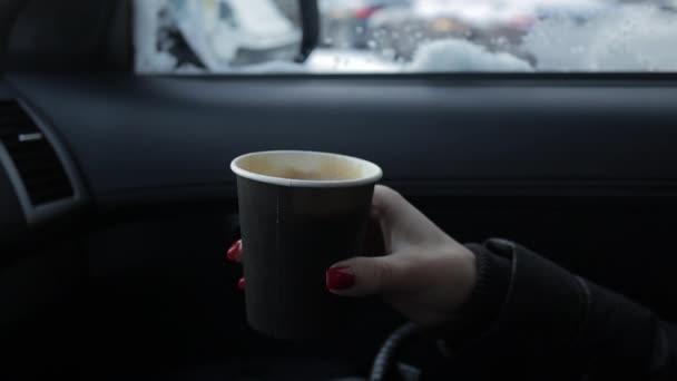 žena pije horký nápoj sedí v autě v zimě