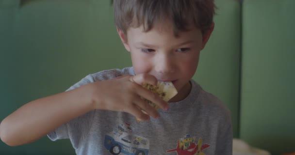 Funny boy in grey t-shirt chews bread Focaccia snack in cafe