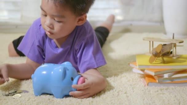 Šťastný asijský kluk školka uvedení pin peníze mince do modrého obličeje selátko štěrbina. Malé dítě dává mince do prasátko banky pro úsporu s hromadou mincí doma, Investiční vzdělávání koncept