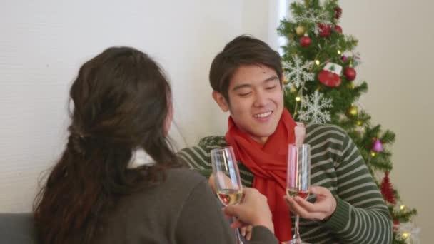Glückliche asiatische schöne junge Familie Paar Mann und Frau auf dem Sofa im heimischen Wohnzimmer, Mann und Frau sitzen Sofa in verliebten klingende Gläser mit Champagner genießen und trinken Winterurlaub zusammen Zeitlupe