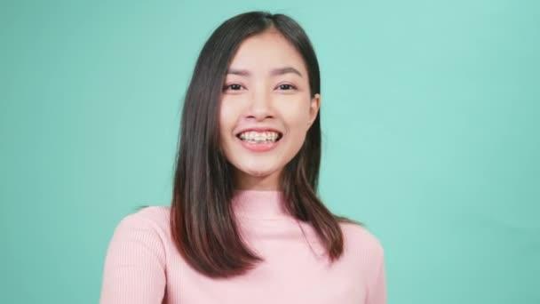 Portrait junge asiatische glückliche schöne Frau lächelnd tragen Silikon kieferorthopädische Halter auf Zähnen zeigt Zähne Modell auf der Hand isoliert auf blauem Hintergrund. Dentalhygiene und Gesundheitskonzept