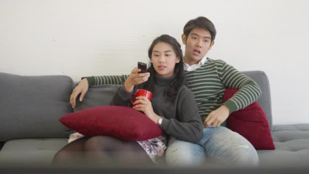 Happy asijské krásný mladý rodina pár manžel a manželka těší v obývacím pokoji zima doma sledování televize zábava nebo film spolu