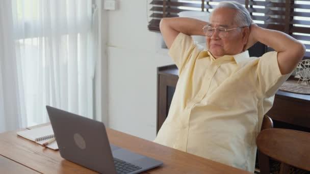Starší muž oblečený nosit brýle sedí na židli pracuje na notebooku v obývacím pokoji doma, Šťastný stařec odešel do důchodu pomocí počítače, Starší dědeček práci z domova, zpomalený pohyb