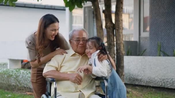 Behinderter Senioren-Opa im Rollstuhl mit Enkelkind und Mutter im Park, Glückliche asiatische Drei-Generationen-Familie, die zusammen im Garten Spaß hat, Opa und kleines Kind lächeln und lachen