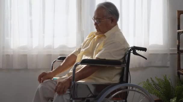 Schwerbehinderte ältere Patienten sitzen allein im Rollstuhl, Traurige und depressive einsame asiatische Senioren fühlen sich einsam und gelangweilt und warten auf Pflege Weißes Zimmer Demenz und Alzheimer
