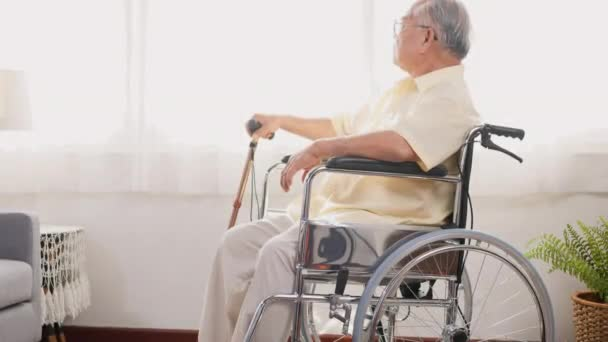 Pensive disabled elderly patient sit on wheelchair alone, Sad and depressed lonely Asian senior old man head down feel lonely and bored waiting for take care white room dementia and Alzheimer