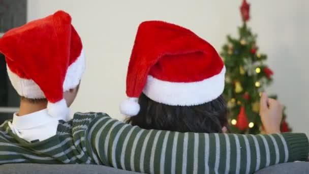 Glückliche asiatische schöne junge Familienpaar Mann und Frau sitzen auf dem Sofa mit einem Weihnachtsmann Hut vor dem Kamin bei warmen Hause Weihnachten Winter umarmen Wohnzimmer, Rückseite,