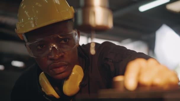 Amerikanische industrielle schwarze junge Arbeiter Mann mit gelben Helm und Gehörschutz manuelle Drehung auf Bohrmaschine, um Werkstück zu durchdringen, Ingenieur bei der Arbeit in der Industrie Fabrik. Zeitlupe