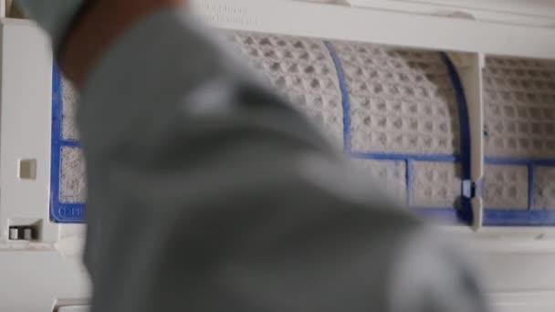 Person entfernt Klimaanlage Filter, Hand des Technikers Mann arbeitet Ziehen staubigen Filter aus Klimaanlage zur Reinigung im Raum zu Hause