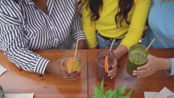 Çok ırklı arkadaşlar, kahveli brunch barında meyve suyu ile kadeh kaldırıyorlar.