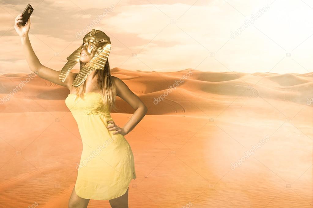Woman in Egyptian sphinx mask take selfie