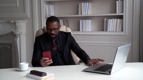 Afroameričan v černém obleku, košili a stylových brýlích. Podnikatel sedí na stolku u laptopu, sedí ve světlé kanceláři a dívá se na telefon.