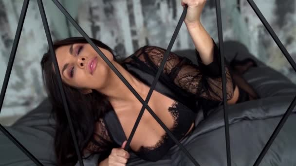 Brunetka leží a pózuje v pokoji na posteli v sexy spodním prádle. Atraktivní žena relaxovat v posteli doma.