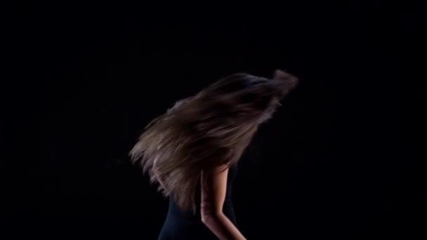 fiatal energikus, műanyag nő egy fekete öltöny a stúdióban egy sötét háttér tánc, mozgó és pózol.