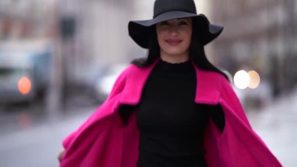 Egy elegáns fekete hajú nő rózsaszín kabátban és fekete kalapban sétál a homályos hátterében egy városi utcának, közel az úthoz. Mosolyog, pózol és forog..