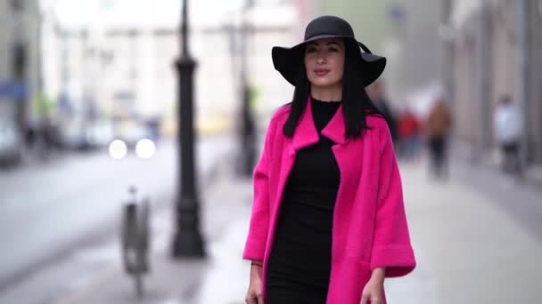 A pretty woman in a pink coat and a black hat walks on a blurry background of a city street. Smiles.