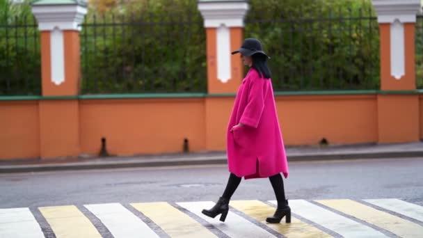 Frau läuft am Herbsttag auf Fußgängerüberweg in der Innenstadt