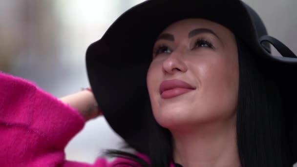 közelkép portré szexi nő tetoválás szemöldök és ajkak, séta az utcán, fekete kalap a fejen
