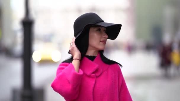 módní je procházka ve městě na podzim, žena má na sobě černý klobouk a jasně růžový kabát