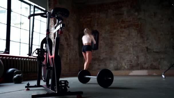 fiatal nő edz egyedül tornaterem, lyukasztó vadászzsák doboz edzés