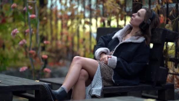 přemýšlivá mladá žena sedí na lavičce na podzim a poslouchá hudbu ve sluchátkách, relaxovat